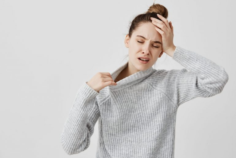 Exhausted girl holding her head with closed eyes being hot. Female office assistant suffering from temperature and fever she needs fresh air. Health concept