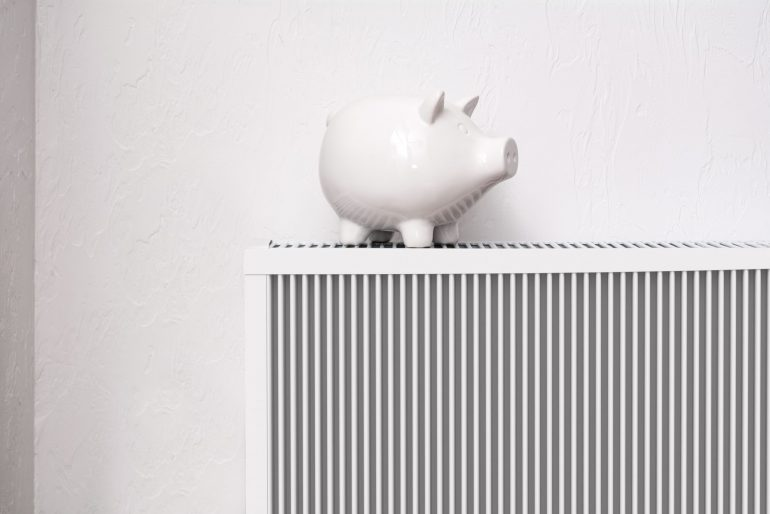 White pig piggy bank on radiator. Expensive heating costs concep